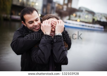 Young handsome man surprising her female partner. - stock photo