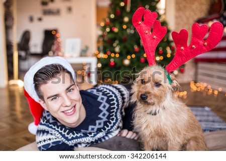 Young handsome man taking a selfie with his dog in front of a Christmas tree. American flag, Depth of field, selective focus  - stock photo