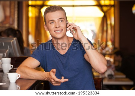 young handsome man talking on phone. handsome guy sitting in cafe and smiling