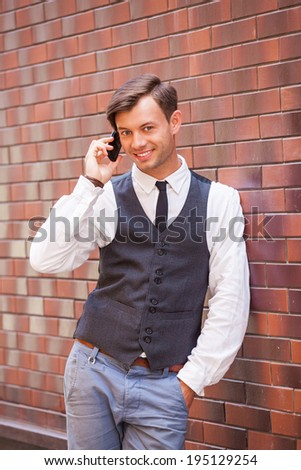 Young handsome man talking on the phone with smile - stock photo