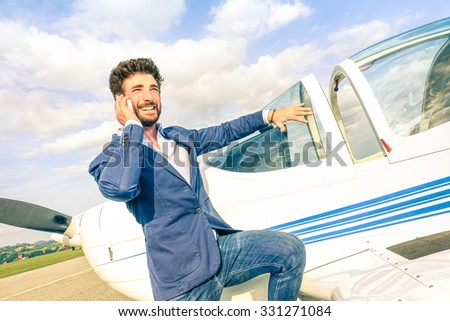 Young handsome man talking with mobile smart phone at private airplane - Modern business concept with confident guy using smartphone at airport. - stock photo
