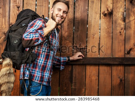 Young handsome man tourist traveler with a marching backpack poses against wooden fence.  - stock photo