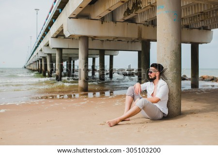Young handsome man traveling alone with back pack, spend time at beautiful laguna surfers beach in California,east coast.Nice sunny day relaxed atmosphere.hiker man  - stock photo