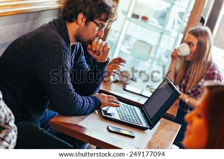 Young Handsome Man Using Laptop In Cafe - stock photo