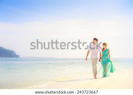 young handsome man walk with beautiful blonde girlfriend in blue dress