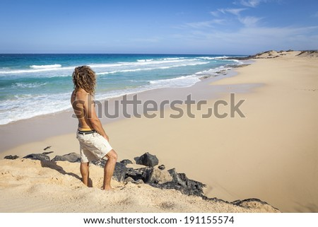 young handsome man walking alone on the beach shore