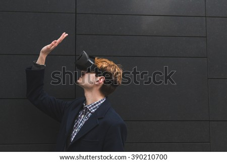 Young handsome man wearing a virtual reality headset - stock photo