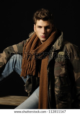 young handsome man wearing coat and scarf. sitting wooden chair