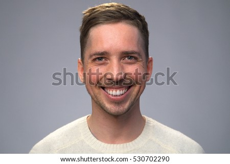Young handsome man with a beautiful smile, gray background