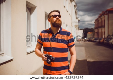 young, handsome man with a camera, dressed in the style of hipster, outdoor portrait photographer in national geographic, travel photo, instagram, vintage retro camera, sunglasses, beard man - stock photo