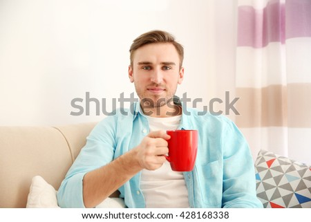 Young handsome man with a cup of coffee at home