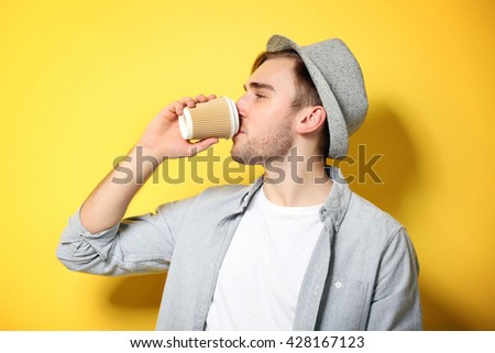 Young handsome man with a cup of coffee on bright yellow background