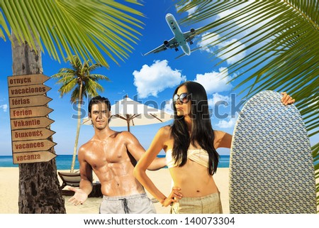 Young handsome man with asian woman holding a surf board - stock photo