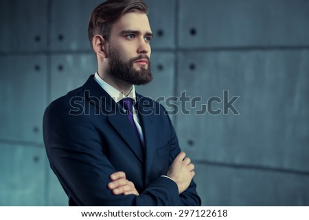 Young handsome man with beard in black suit looking aside. - stock photo