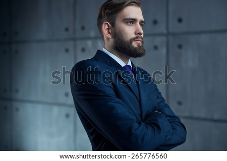 Young handsome man with beard in black suit looking outside to window. - stock photo