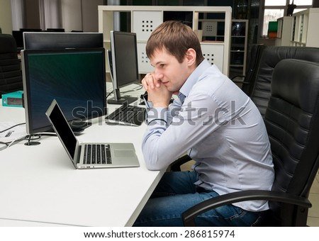 Young handsome man with computer in the office. Programming code. Thinking over task