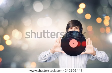 Young handsome man with disco plate in hands