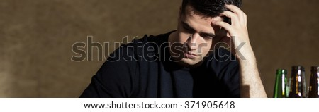 Young handsome man with drinking alohol problems - stock photo