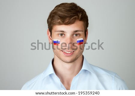 young handsome man with flag of Russia painting at face - stock photo