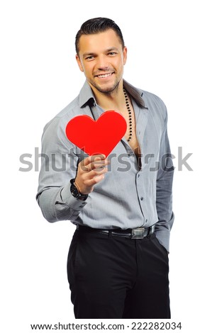 Young handsome man with heart shaped toy - stock photo