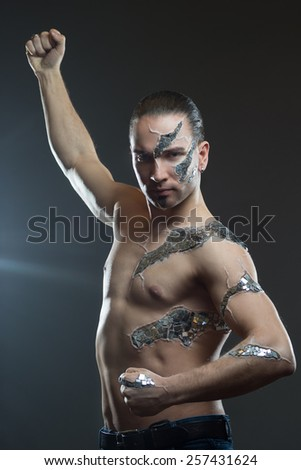 Young handsome man with  mosaic body art, standing in front of black background: body-art project - stock photo