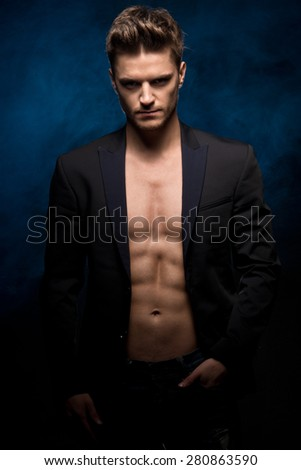 Young handsome man with muscle abdominal and open jacket.   - stock photo