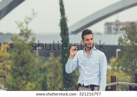 Young handsome man with short hair and beard wearing suspenders and posing in an urban context