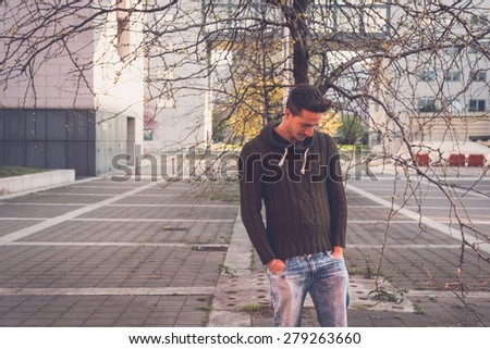 Young handsome man with short hair posing in an urban context