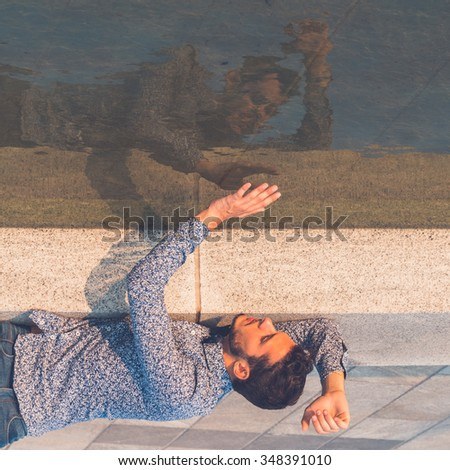 Young handsome man with short hair wearing a bow tie and looking at himself in the water - stock photo