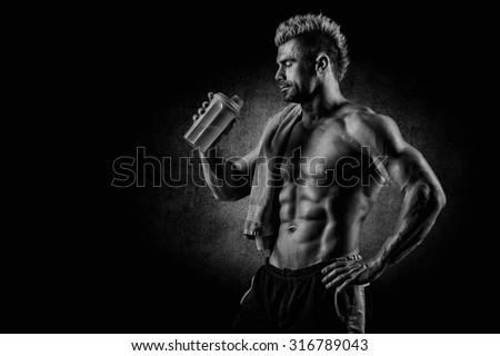 young handsome man with strong muscles, protein drink after training