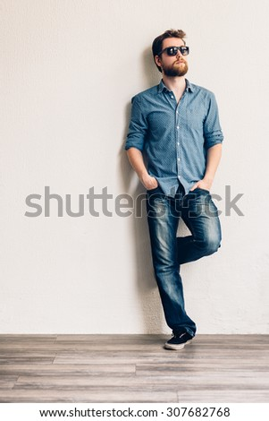 Young handsome man with sunglasses,  leaning against a white wall. - stock photo