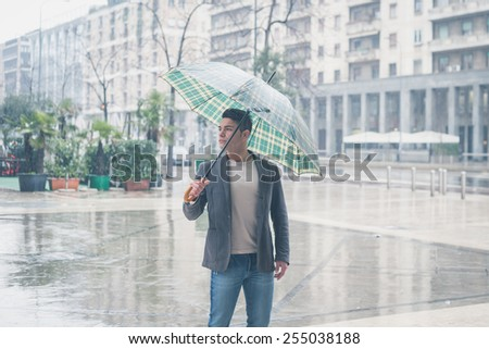 Young handsome man with umbrella posing in the rain - stock photo