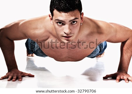 young handsome man working push ups, studio shot