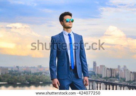 Young handsome masculinity businessman dressed in a blue suit. He stands against the backdrop of a beautiful, textured sky with clouds and the city. And looking to the side.