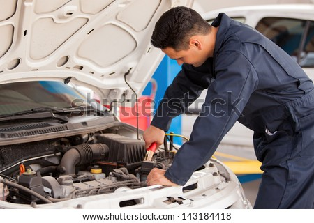 Young handsome mechanic putting some jumper cables on a battery before jump starting it - stock photo