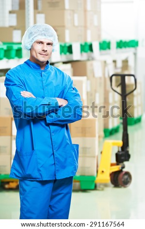 young handsome medical warehouse worker man in front of boxes with medcine drugs stack arrangement - stock photo