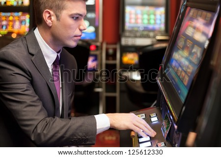Young handsome men gambling in the casino on slot machines - stock photo