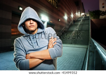 Young handsome men in a hood outdoors - stock photo