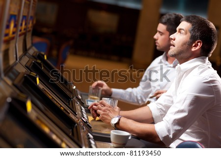 young handsome men playing the slot machine in a casino