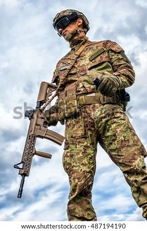 Young handsome military man holding automatic rifle and hand grenade on sky background. Airsoft