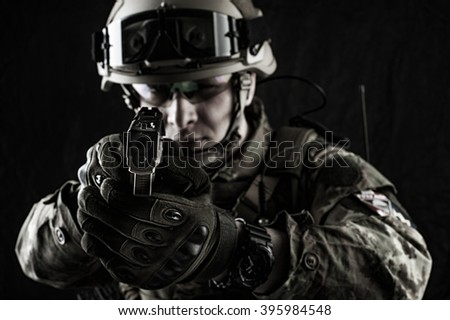 Young handsome military man in italian camouflage aiming from handgun, he wearing helmet, glasses and radio set. Focus on the gun muzzle