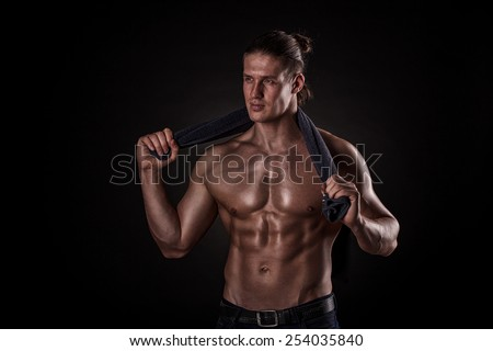 young handsome muscular guy with a towel around his neck - stock photo