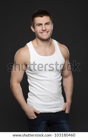 Young handsome muscular man in white t-shirt posing with his hands in pockets over dark background - stock photo