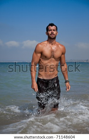 Young handsome muscular man walking out of the water in a tropical beach wearing a bathing suit - stock photo