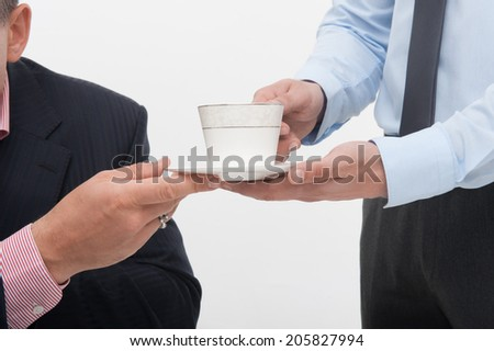 Young handsome office worker assistant brings coffee cup to senior manager, closeup portrait isolated on white - stock photo