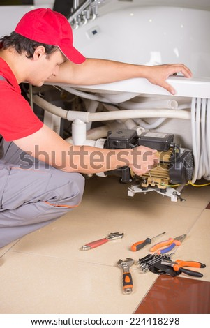 Young handsome plumber is repairing bathtub. Service. - stock photo