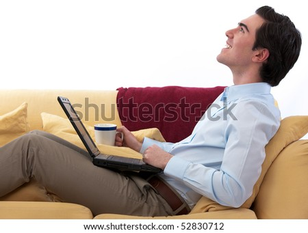 Young, handsome professional working from home on his sofa against white background - stock photo