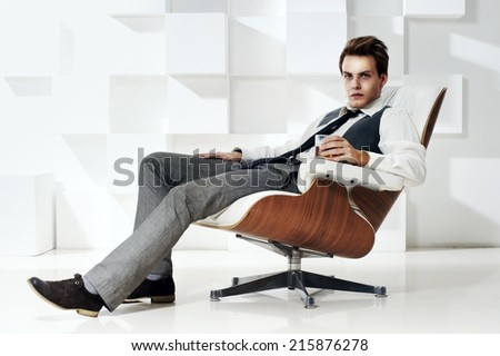 Young handsome rich successful man sitting in expensive leather and wooden chair with glass of whiskey and looking in camera. Fashion portrait in modern interior - stock photo