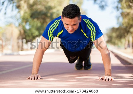 Young handsome runner warming up and doing some push ups as part of his training - stock photo