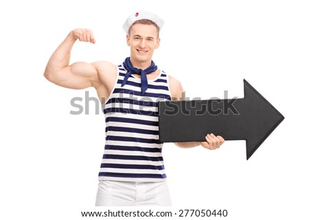 Young handsome sailor showing his bicep and holding a big black arrow pointing right isolated on white background - stock photo